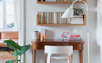 small study, wooden table, white wall, wooden floating shelves, white floor lamp, white wooden chair