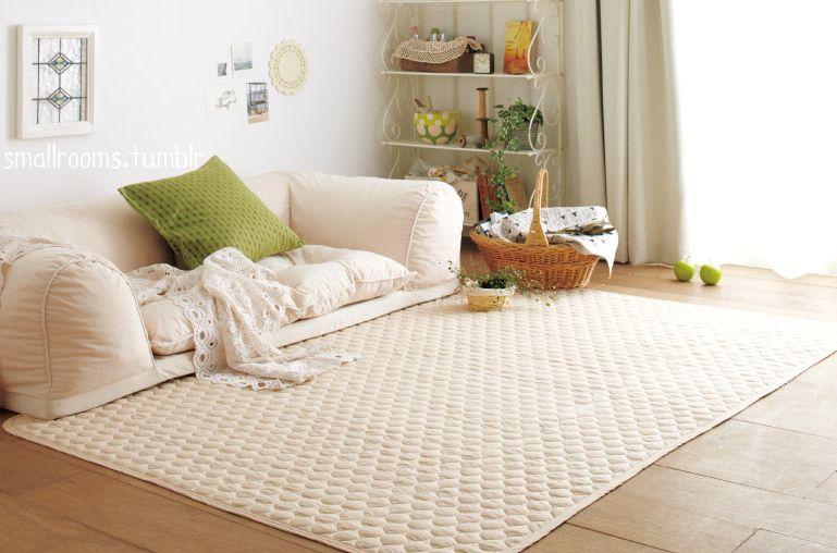 white floor seating, wooden floor, white rug, white wall, white shelves