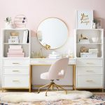 White Modern Table With Drawers, White Shelves, White Cabinet, Pink Office Chair With Golden Legs, Gold Framed Round Mirror