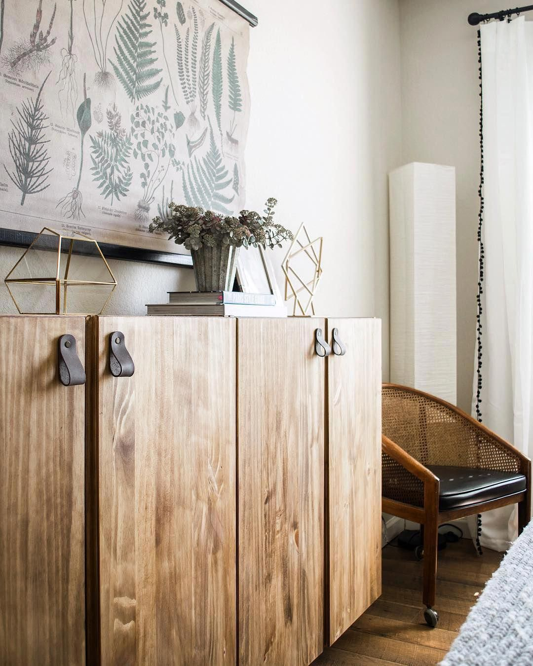 wooden cabinet, wooden floor, white wall, wooden chair with black leather cushion