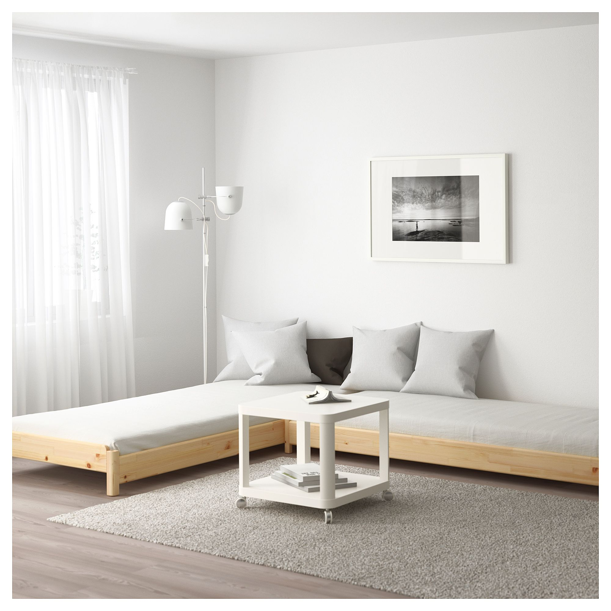 wooden corner sofa with white cushion, wooden floor, grey rug