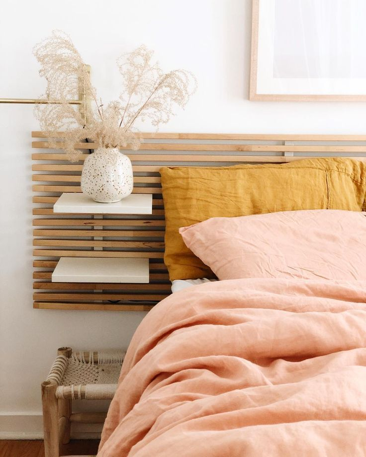 wooden grid headboard, white floating shelves, wooden side table, peach bedding, mustard pillows