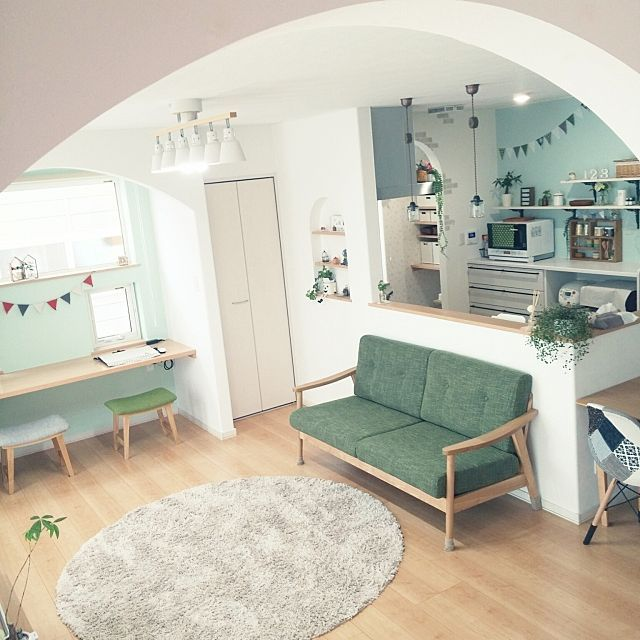wooden sofa with green cushion, wooden floor, white wall, wooden floating table, green stools, white pendants