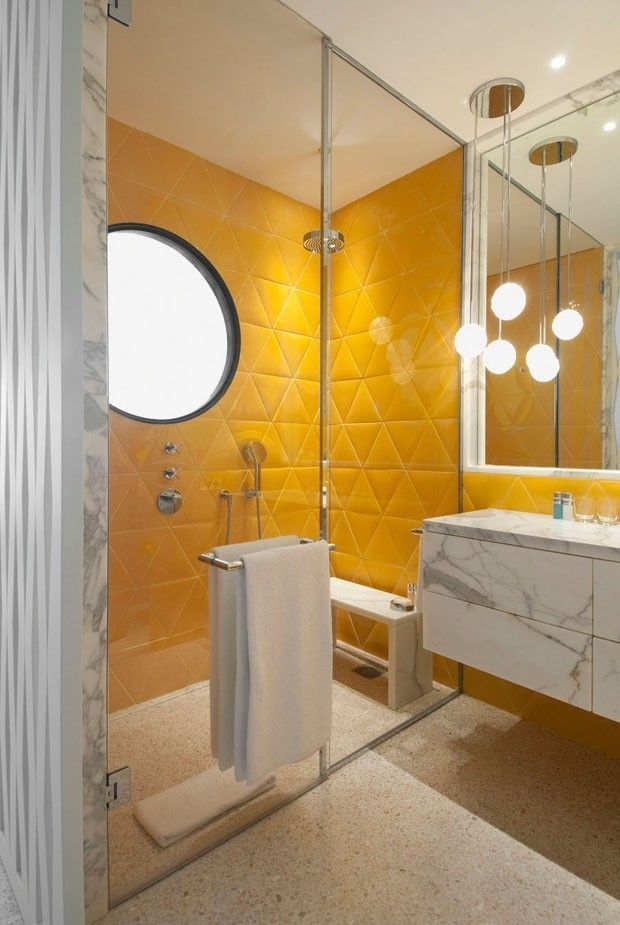 yellow bathroom, grey wall, yellow triangle tiles on the wall, white marble floating cabinet, pendant, marble bench, round mirr