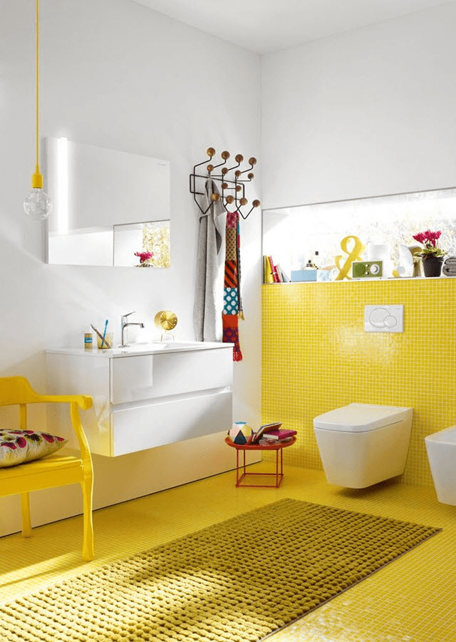 yellow bathroom, yellow tiny tiles as floor and accent wall, white wall, white floating cabinet, white toilet, yellow chair, mirror
