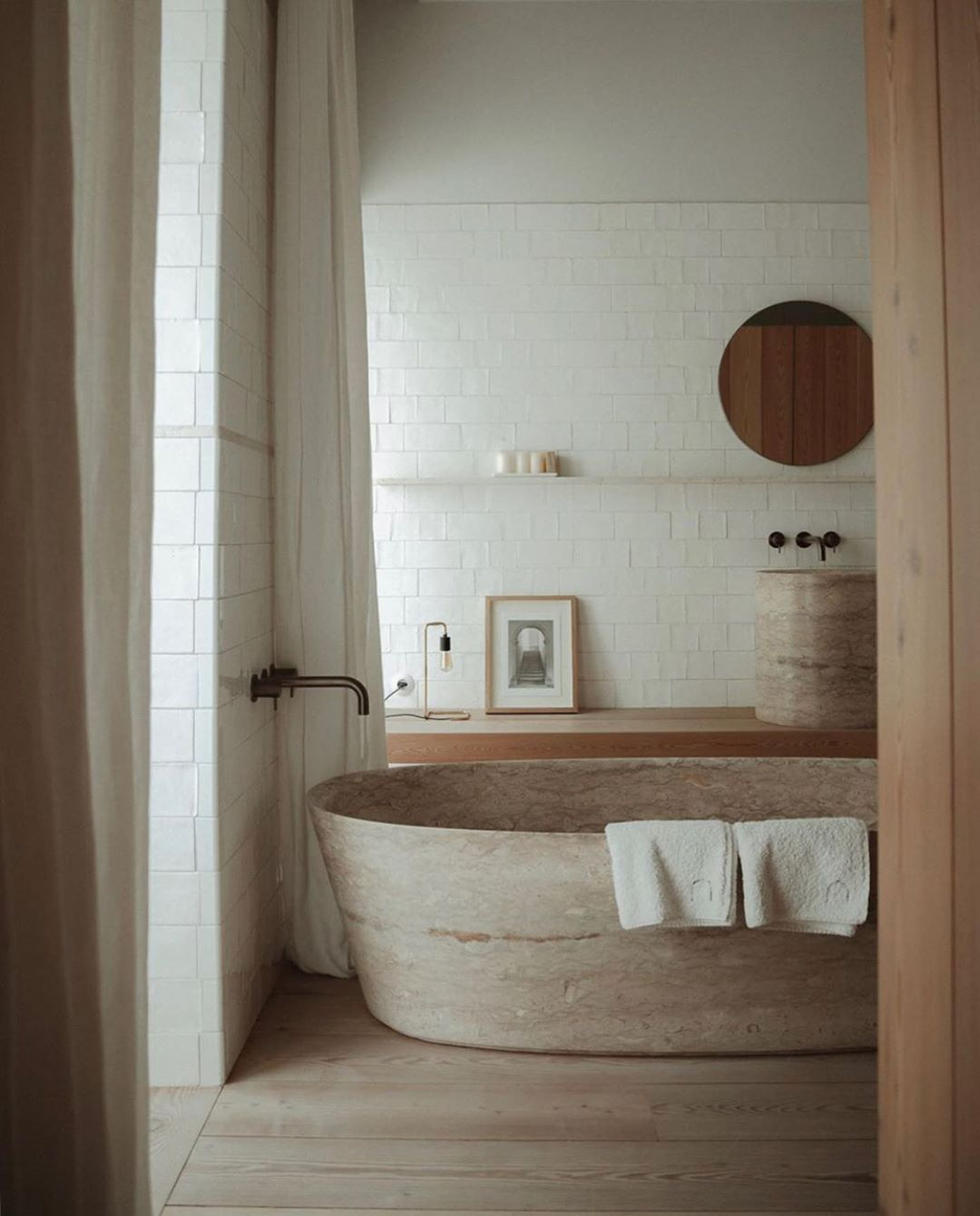 bathroom, brown stone floor tiles, white subway wall tiles, brown stone tub, wooden floating vanity, brown marble round tall sink, round mirror