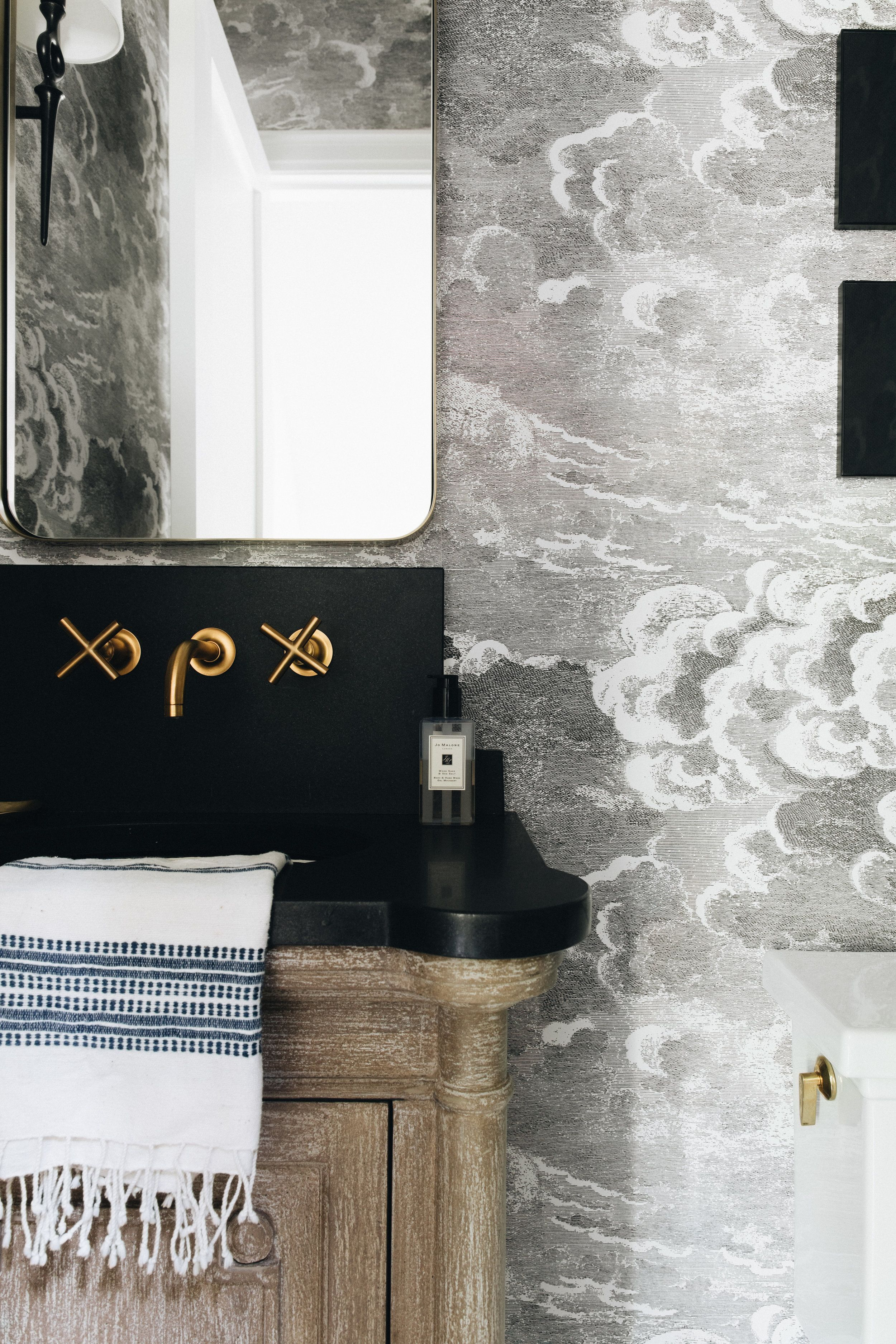 bathroom, grey cloud wall, wooden vanity, black top, golden faucet