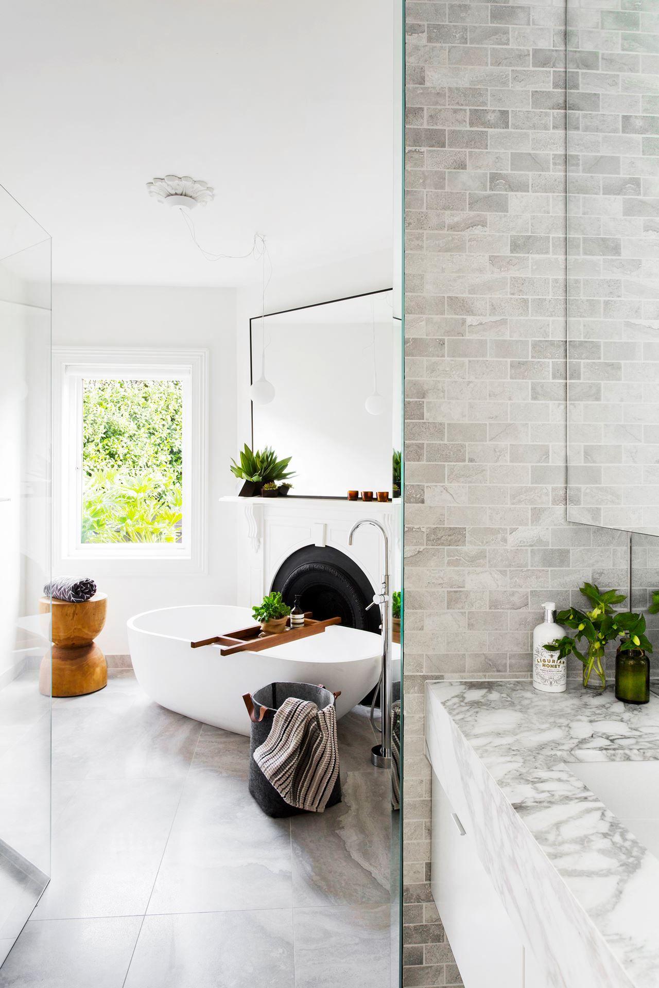 bathroom, grey marble floor, white wall, white tub, big rectangular mirror, grey wall tiles, grey marble vanity