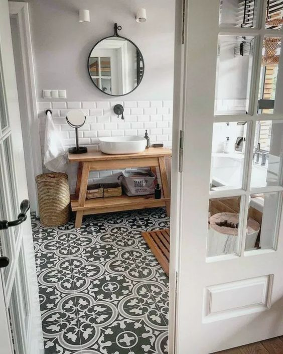 bathroom, grey patterned floor, white wall tiles, wooden vanity table, white sink, round mirror