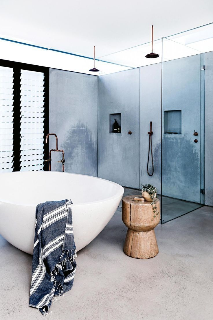 bathroom, grey seamless floor, grey wall, white bowl sink, wooden side table, shower area, glass partition