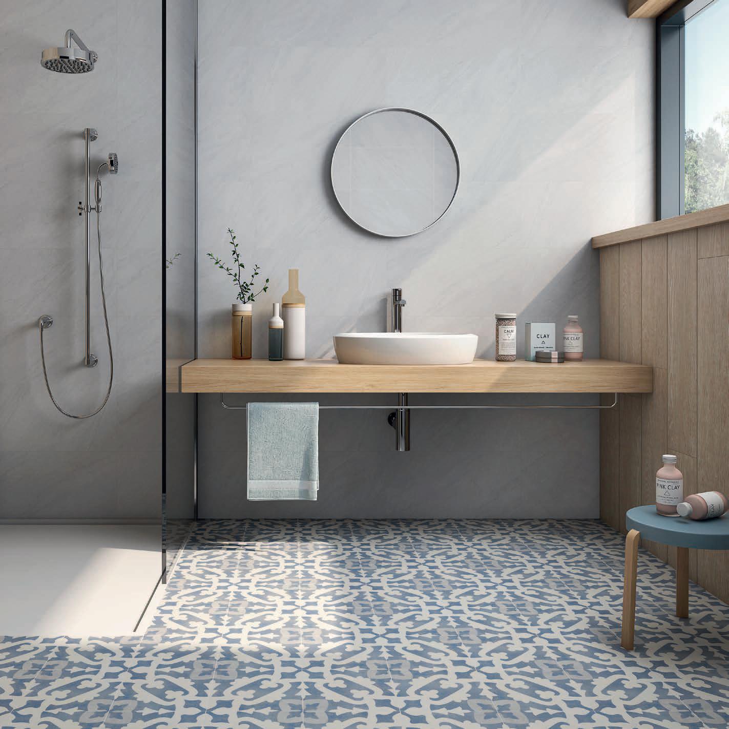 bathroom, grey wall, white shower floor, round mirror, wooden floating vanity, white sink, blue patterned floor, wooden wall