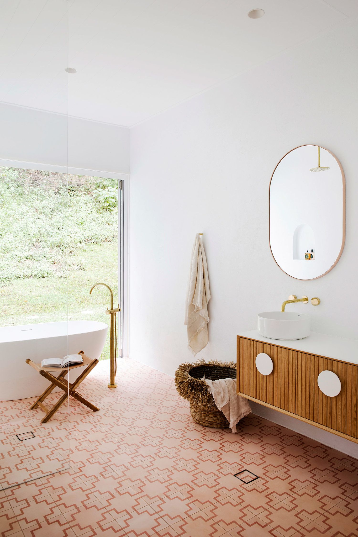 bathroom, orange patterned floor, white wall, wooden floating cabinet with white top, white round sink, ovale mirror, white tub, golden faucet