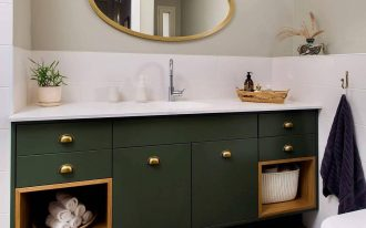 bathroom, patterned floor tiles, white wall tiles, dark green cabinet with white top, ovale mirror, white toilet