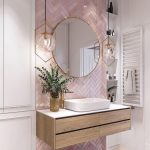 Bathroom Vanity, Pink Herringbone Pattern, Glass Pendants With Golden Frame, Wooden Floating Vanity With White Top, White Sink, Golden Faucet, Round Mirror With Golden Frame