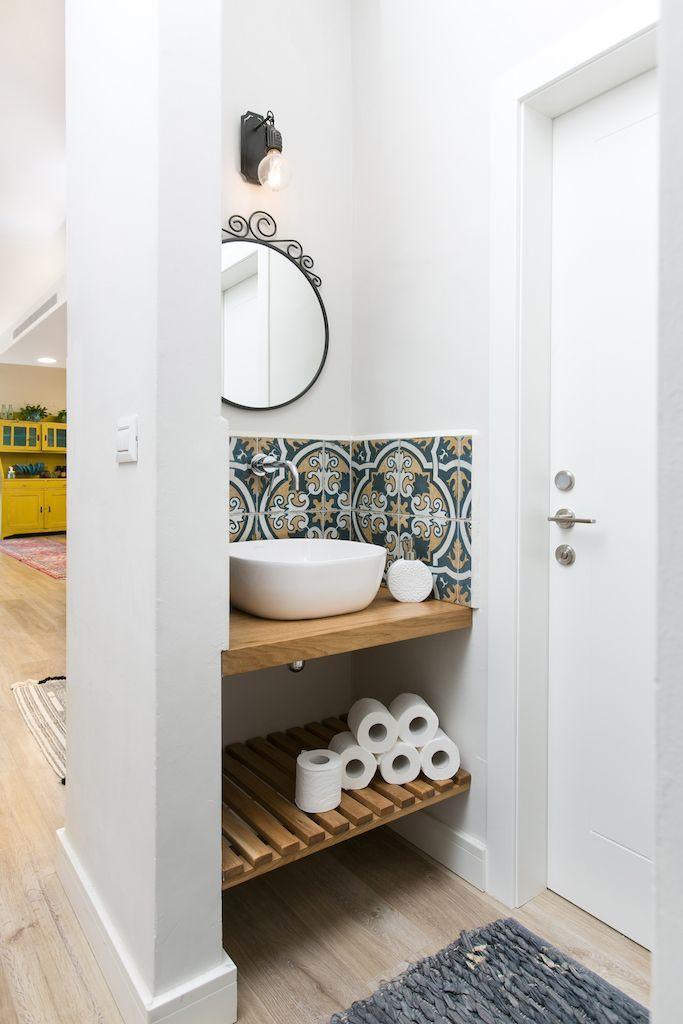 bathroom vanity, white wall, blue patterned backsplash tiles, wooden floating vanity, wooden floating rack, round mirror