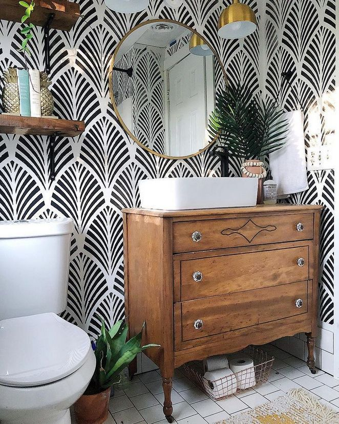 bathroom, white floor tiles, black white patterned wall tiles, white sink, wooden cabinet, white toilet, round mirror, golden sconce