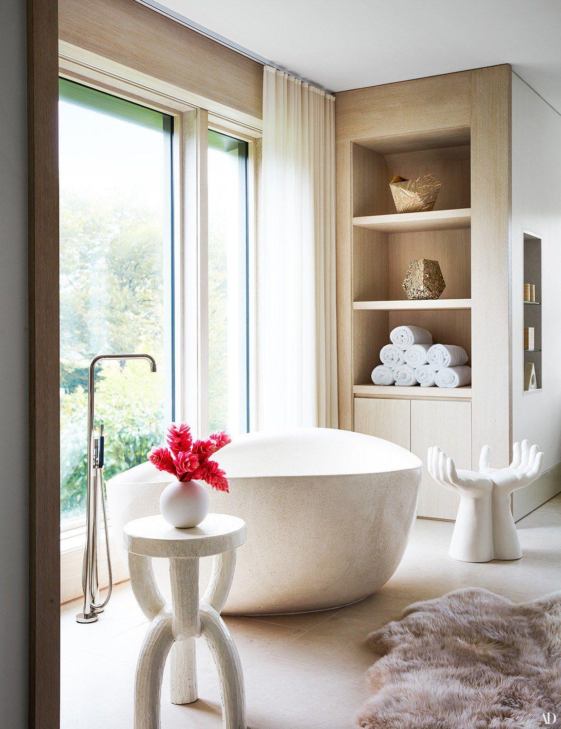 bathroom, white floor tiles, white bowl sink, white side table, white unique stool, built in shelves, glass wall