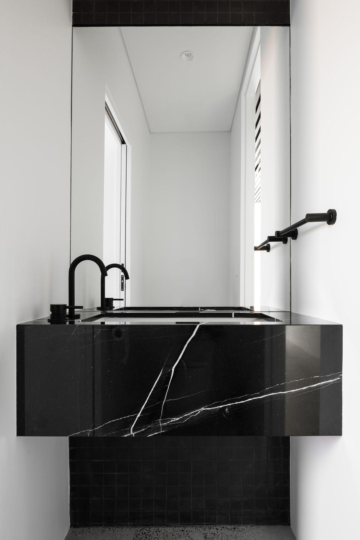 bathroom, white wall, black marble vanity, indendted sink, black faucet, black cabinet