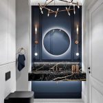 Bathroom, White Wall, White Cabinet, White Marble Floor, Dark Blue Accent Wall, Black Marble Floating Vanity, Indented Sink, Round Mirror, Thin Sconce, Thin Chandelier