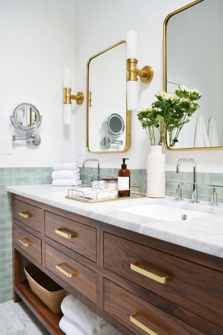 bathroom, wooden vanity cabinet, white marble top, white wall, green subway tiles, white sconces with golden accent, mirror with golden frame