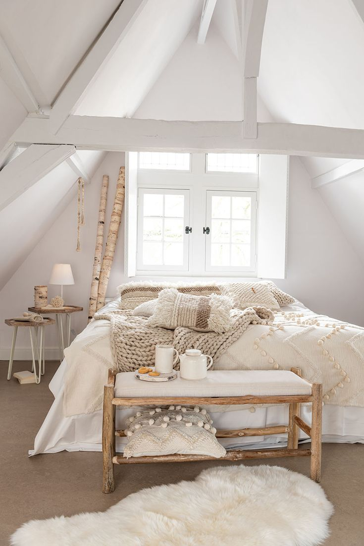 bedroom, brown rug, white vaulted ceiling, white bedding, side table, wooden bench with white cushion