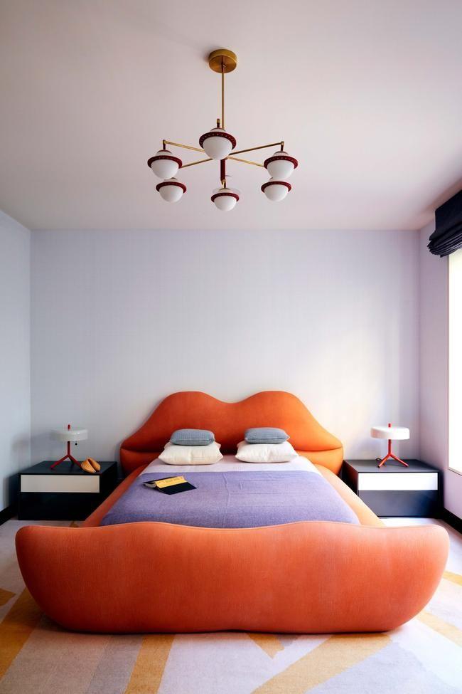 bedroom, white floor, white wall, white modern chandelier, orange bed frame, orange lip head board, green side cabinet