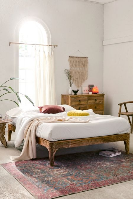 bedroom, white wall, off white floor, patterned rug, wooden bed platform, wooden cabinet, wooden chair, wooden side table