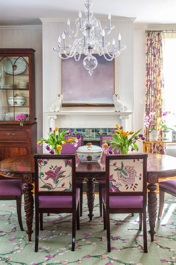 dining room, green flowery rug, wooden chairs, purple cushion, wooden table, white wal, chandelier, patterned curtain