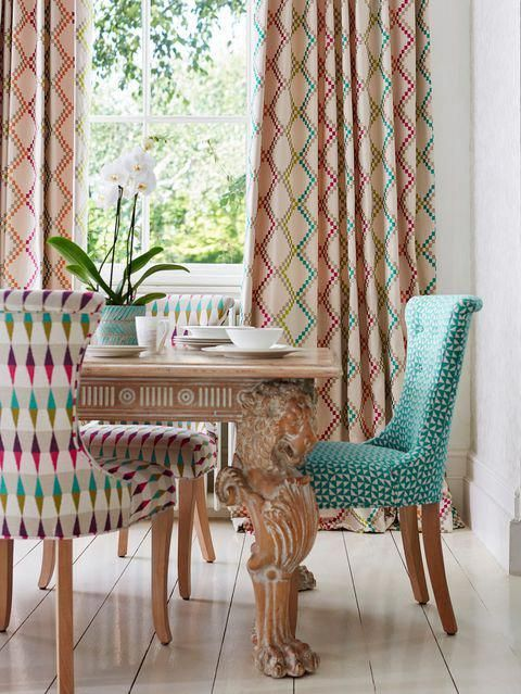 dining room, white floor tiles, white wall, wooden table, wooden chairs with colorful cushion, colorful curtain