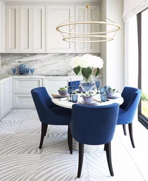 dining room, white floor, white wall, white patterned rug, pendant, white round table, blue chairs, white kitchen cabinet, white marbled backsplash