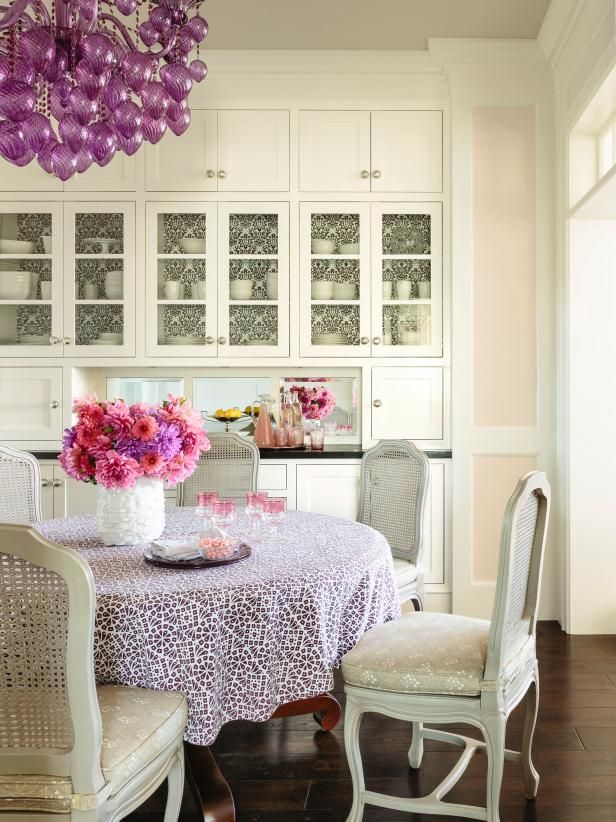 dining room, wooden floor, white kitchen cabinet, light peach wall, round table with white cloth, white chairs, purple chandelier