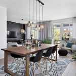 Dining Room, Wooden Floor, White Wall, White Ceiling, Glass Pendants, Wooden Table, Black Modern Chairs, Patterned Rug,