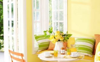 dining room, wooden floor, yellow built in bench, white round table, yellow wall, white window frame