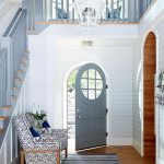 Entrance, White Wooden Wall, Blue Wooden Door With Round Top And Glass, Wooden Floor, White Blue Chair, Blue Striped Rug