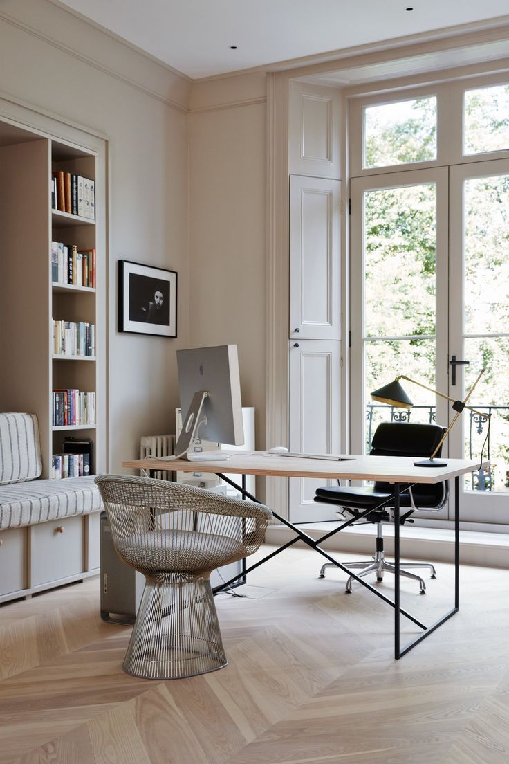 home office, wooden floor, white built in bench, white cushion, white built in shelves, wooden table with black metal legs, metal framed chair with white cushion, black chair