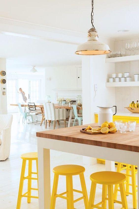 kitchen, white floor, white wall, wooden table, yellow stools