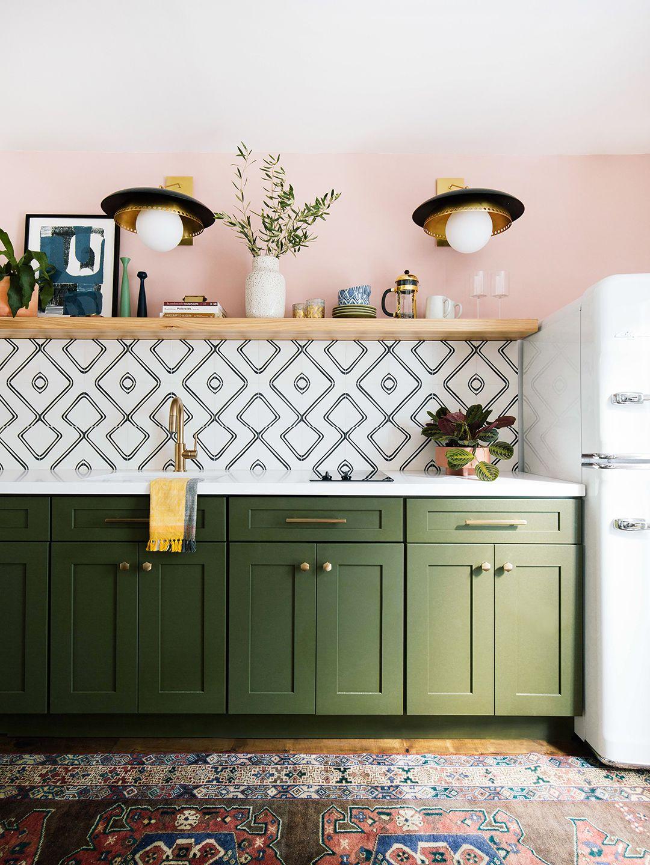 kitchen, wooden floor, patterned rug, pink wall, wooden floating shelves, golden pendants, green kitchen cabinet, white top