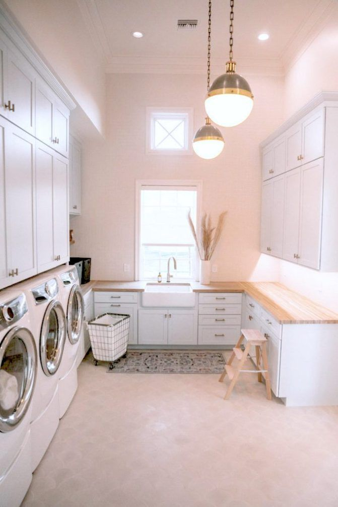 laundry room, cream floor, white cabinet with wooden top, white apron sink, white pendants, white cabinet, white washing machine