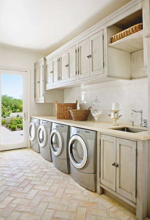 laundry room, cream herringbone floor, white backsplash, cream cabinet, grey washing machine, glass door