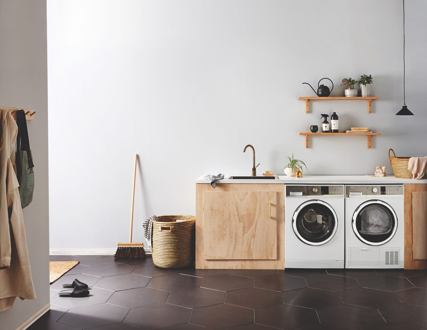 laundry room, grey floor, white wall, wooden cabinet, white wasing machine, wooden floating shelves, black pendant