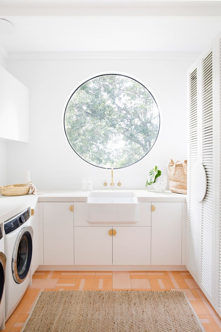 laundry room, orange patterned floor, white wall, white cabinet, white apron sink, round glass window, white cabinet