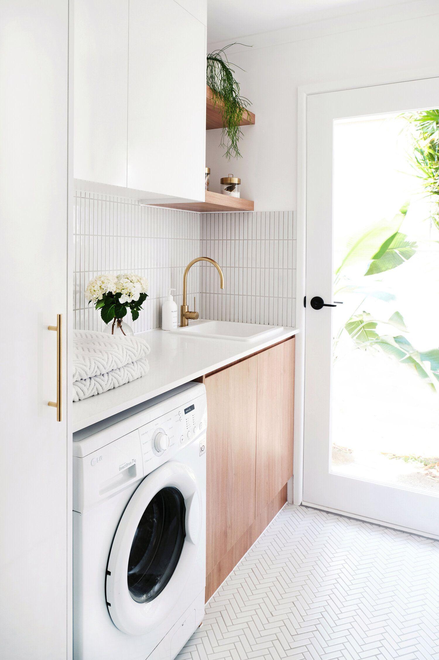 laundry room, white floor tiles, white wall tiles, white cabinet, wooden floating shelves, wooden cabinet, white top, white wall, white washing machine