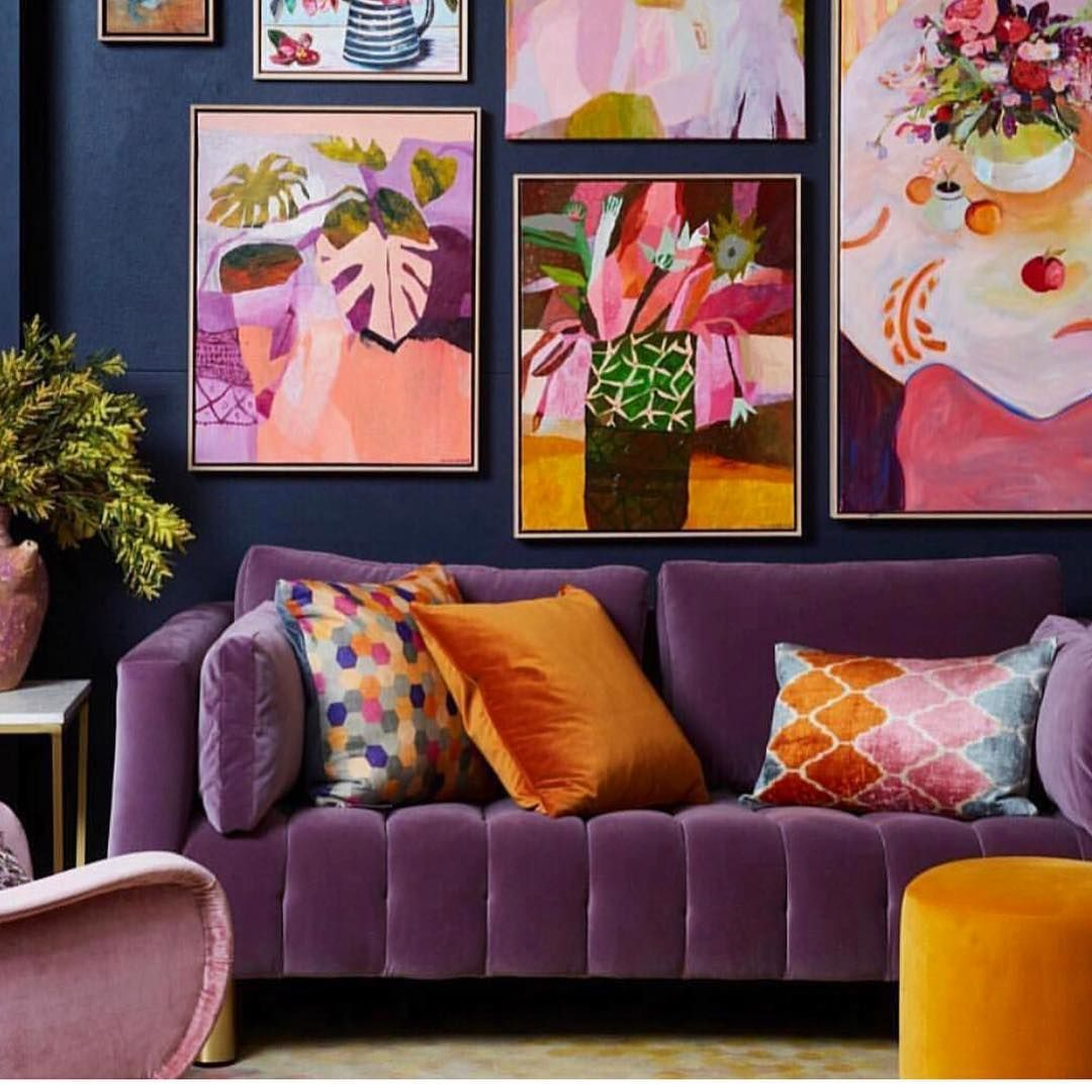 living room, blue wall, brown floor, purple sofa, patterned pillows, pink chair, yellow ottoman