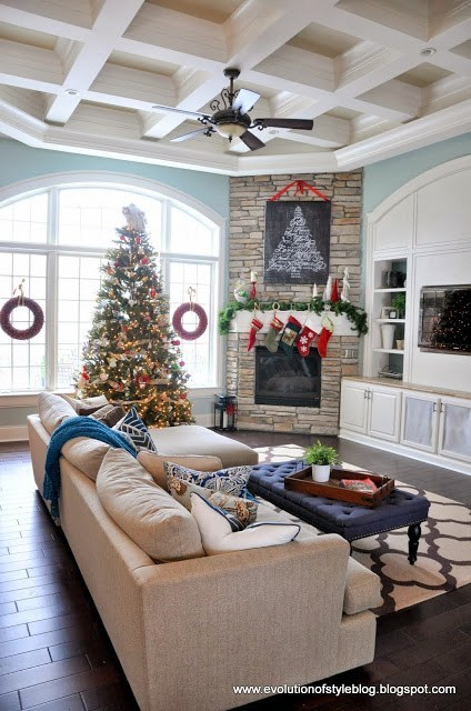 living room, dark floor, blue wall, brown sofa, ottoman table, brown brick fireplace, white cabinet