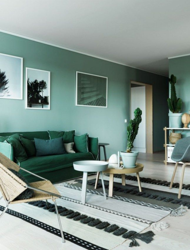 living room, green sofa, turquoise wall, tra tables, black and white rug, gry floor