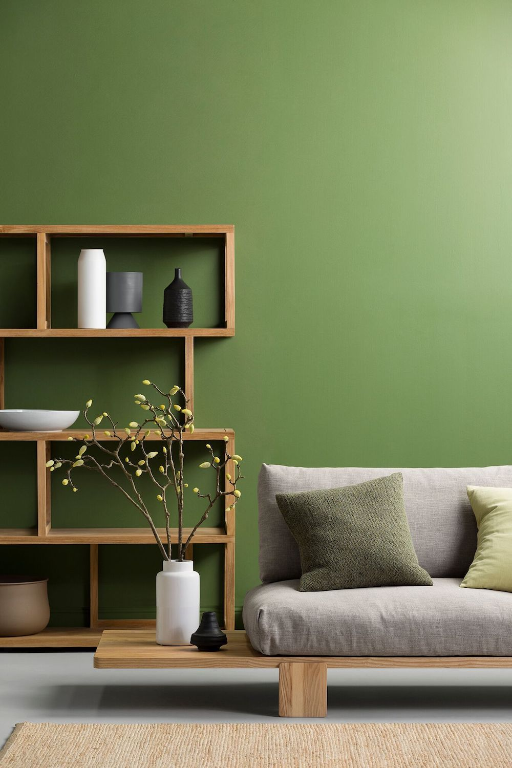 living room, green wall, wooden bench with grey cushion, wooden shelves, seamless grey floor, rattan rug