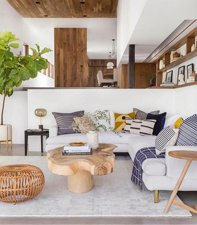 living room, grey floor, grey rug, white half wall, white cornered sofa, wooden coffee table, wooden side table, rattan round ottoman