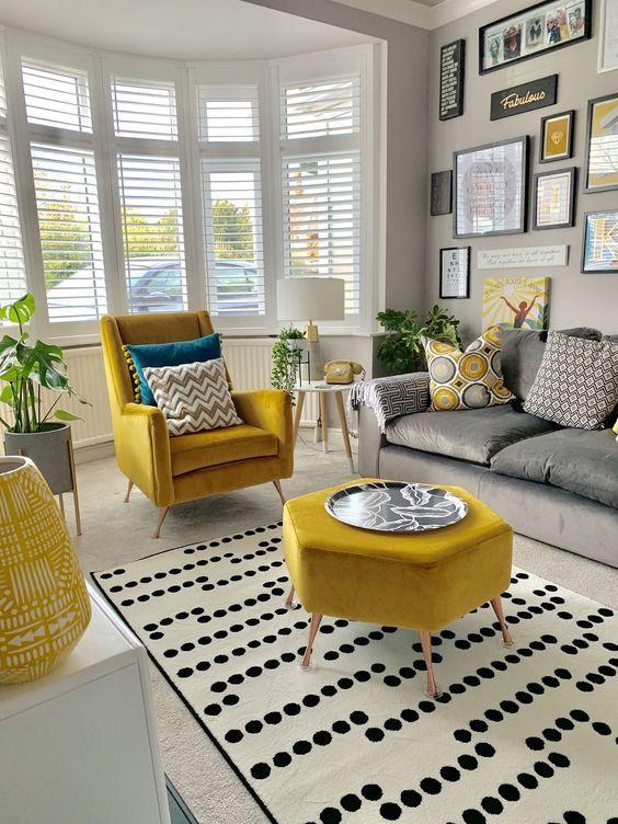 living room, grey rug, white patterned rug, grey sofa, yellow chair, yellow hexagonal ottoman, white cabinet