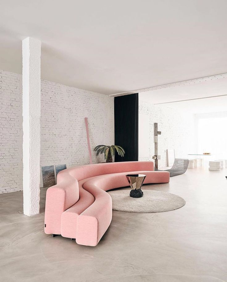 living room, seamless floor, white exposed wall, pink curvy sofa, round beige rug