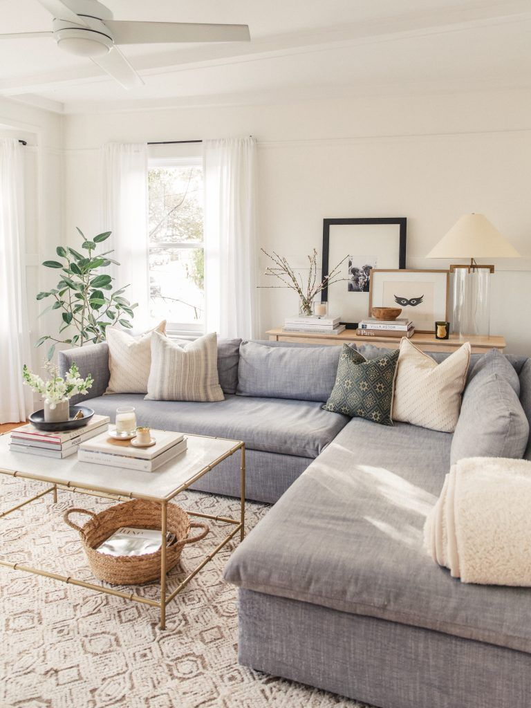 living room, white patterned rug, grey sofa, pillows, white coffee table
